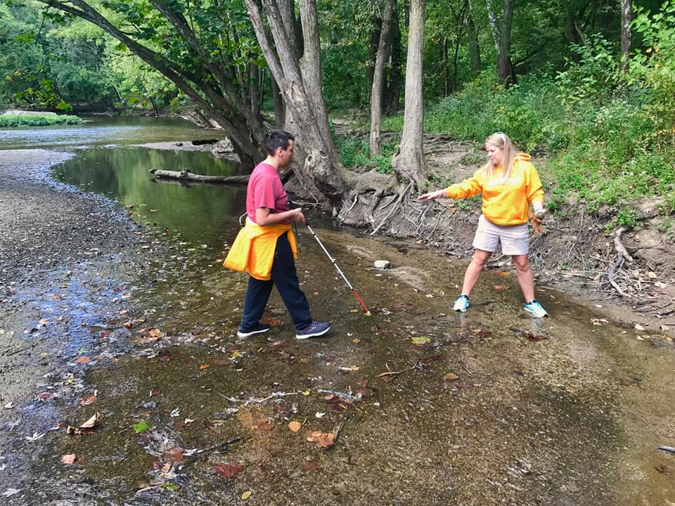 Student helped by teacher across stream