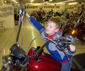 a kid sitting on a motorcycle