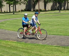 two kids riding a bicycle built for two