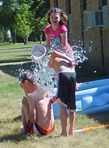 kids dumping water from a bucket on each other